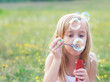 Little girl blowing soap bubbles on spring meadow