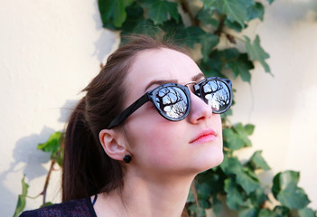 Close-up portrait of beautiful woman in black sunglasses