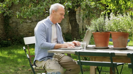 Mature male at table in garden working on laptop computer