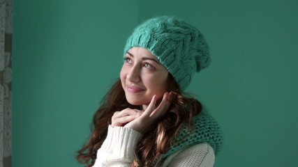 smiling girl in a turquoise knitted hat posing on camera