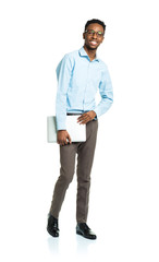 Happy african american college student with laptop standing on w