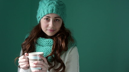 Beautiful girl in a knitted hat holding a mug