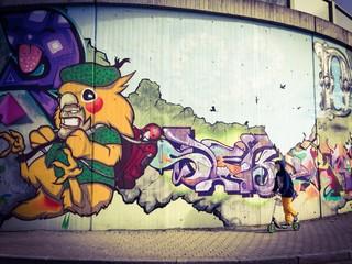 Junge fährt Roller an Graffiti Wand
