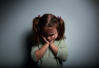 Crying kid girl holding face the hands and looking down
