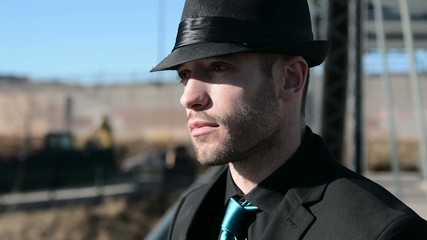Closeup of a handsome young man in a hat and suit