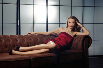 Beautiful lady in red dress is laying on the sofa