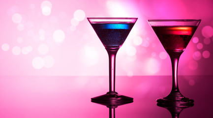 Colorful cocktails on reflective top, with bokeh background