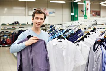 Man chooses shirt in shop