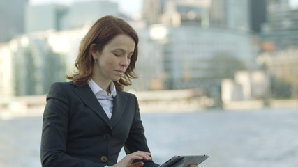 Business woman types and searches on her digital digital tablet /ipad in front of the River Thames