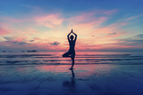 Woman standing at yoga pose on the beach during.
