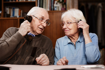 Senior couple with old telephone and smartphone