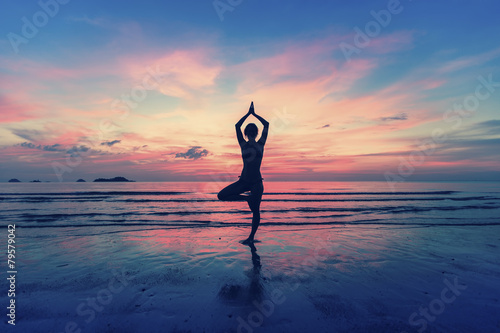 Woman standing at yoga pose on the beach during. - 79579042
