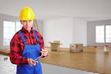 Handwerker mit Zollstock in Zimmer bei Renovierung