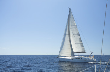 Sailing boat yacht or sail regatta race on blue water.