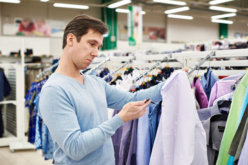 Surprised man looking at price tag of goods