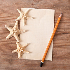 sheet of old paper, starfish on old wooden background