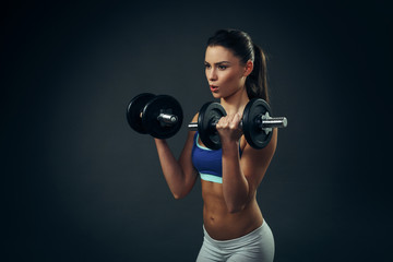 Beautiful young woman exercise with dumbbells on dark background