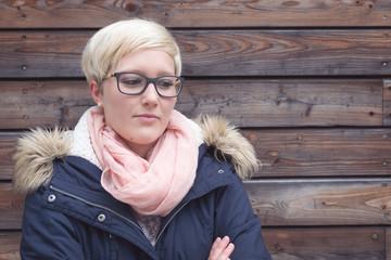 Sorgenvoll blickende junge Frau vor Holzwand