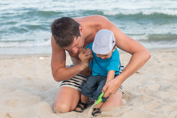 father and son playing at the beach