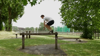Male exercising on balance beam in fitness trail