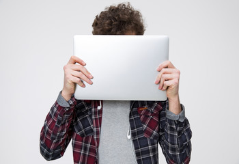 Young man covering face with laptop over gray background