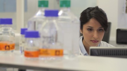 Female scientist working on computer and looks at screen in laboratory