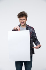 Smiling man with curly hair holding blank billboard