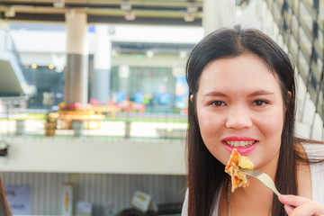 Asain woman eat pizza in restaurant