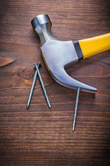 claw hammer with yellow handle and nails on vintage wooden board