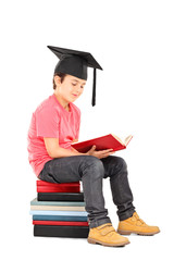 Kid with mortarboard reading a book