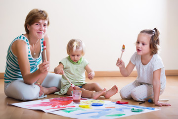 mother and children painting with paint
