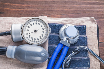 stethoscope and blood pressure monitor on vintage wooden board