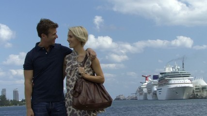 Romantic couple near a harbour with cruise ship in background