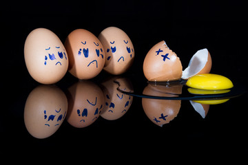 Broken egg on shiny black surface with friends being sad