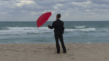 Male opening an umbrella on a beach