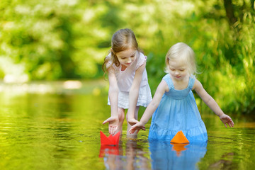 Two sisters playing with paper boats by a river