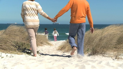 LS REAR VIEW OF GRANDCHILDREN RUNNING ONTO THE BEACH AND THEIR GRANDPARENTS FOLLOWING BEHIND