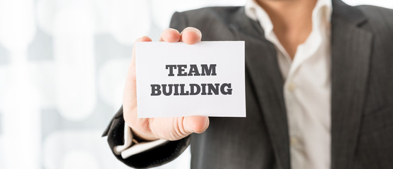 Businessman Showing Card with Team Building Texts