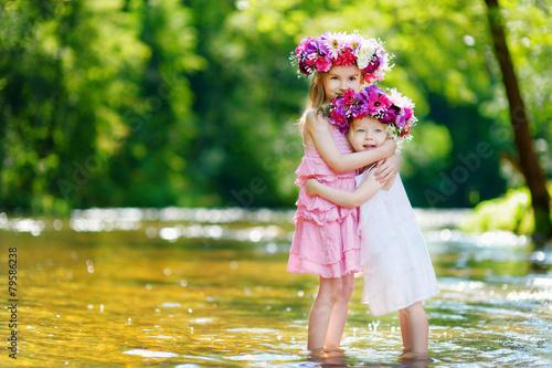 Leinwanddruck Bild Two little sisters wearing flower crowns