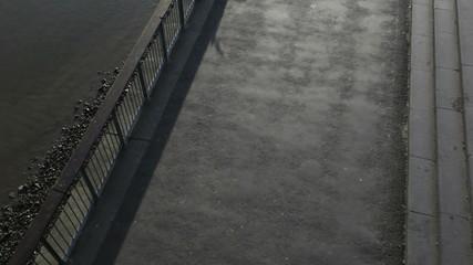 Runner on embankment under millenium bridge, London, UK