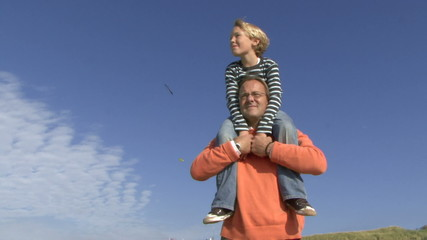 MS Father carrying son (10-12) on shoulders