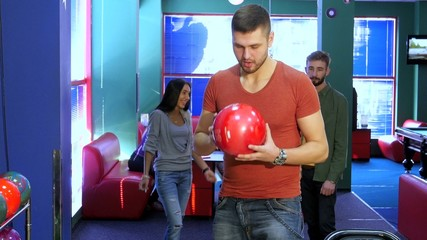 Happy group of friends bowling and holding balls. The joy of