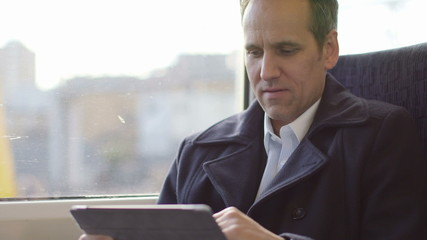 Business Man types and researches on his ipad/digital digital tablet whilst travelling through the city