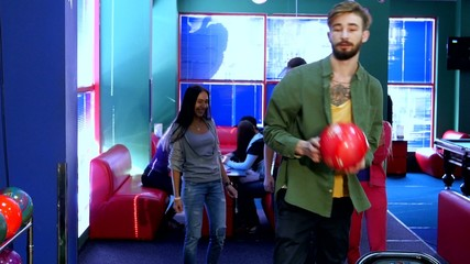 Young man in tattoos rolls the ball, bowling lane. Company