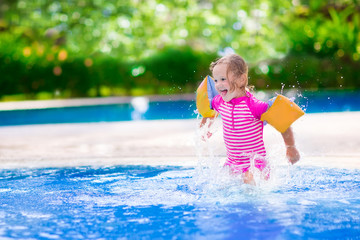 Little girl playing in a pool