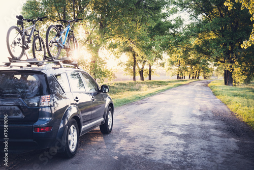 Fotobehang Oost Europa Car with bicycles in the forest road
