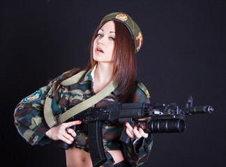 Woman in a military uniform with an assault rifle