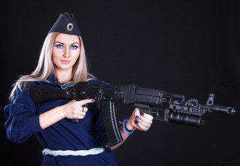Beautiful young woman in a marine uniform with an assault rifle