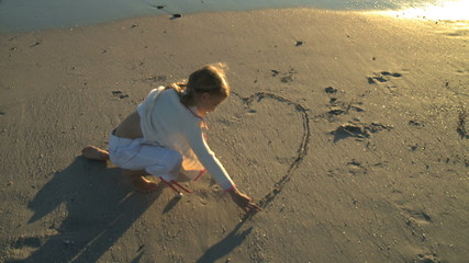 LS OF A GIRL DRAWING A HEART IN THE SAND