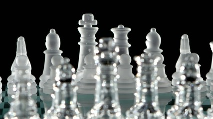 Chess pieces is standing on glass  board. Close up